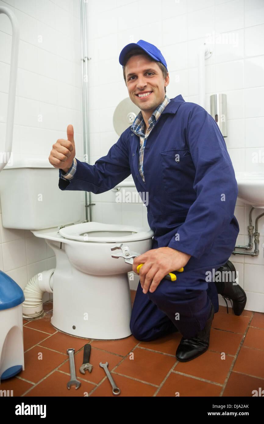 Fontanero arrodillado junto al lavabo mostrando pulgar arriba Imagen De Stock
