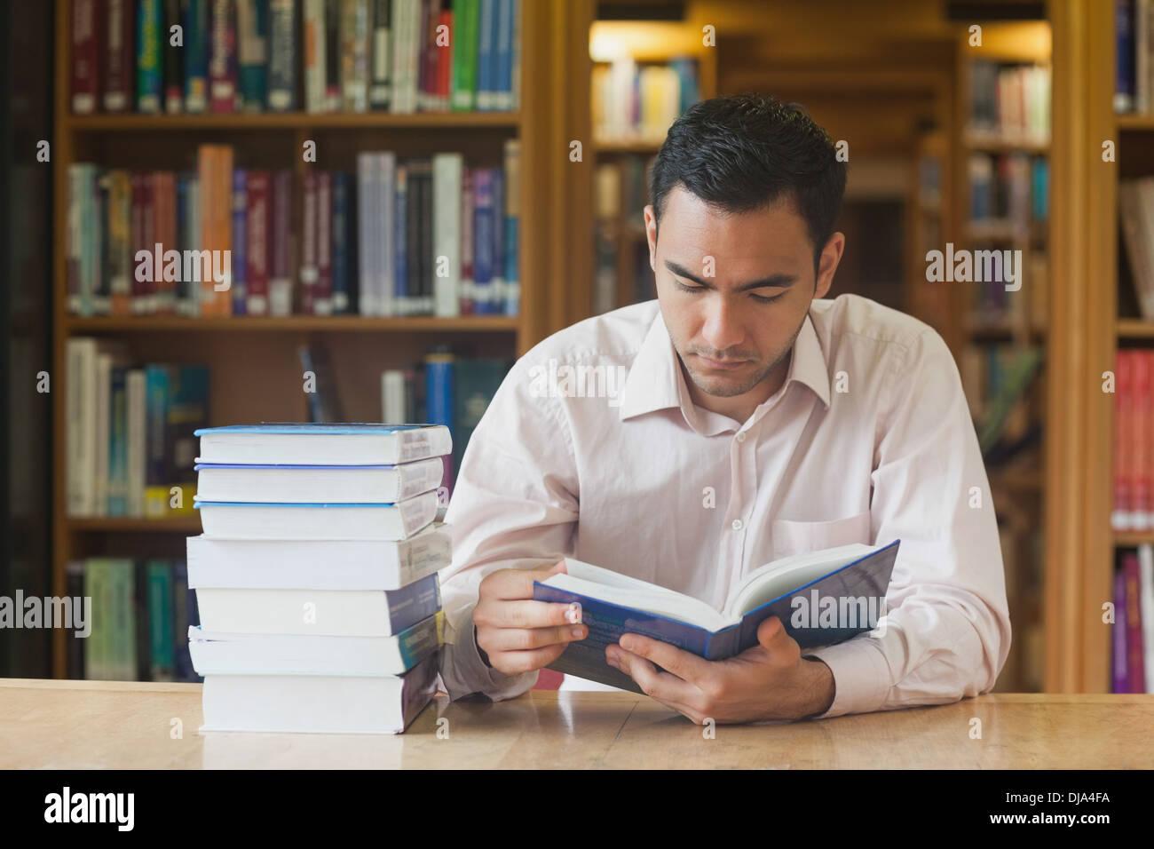 Atractivo intelectual hombre leyendo un libro concentrado Foto de stock