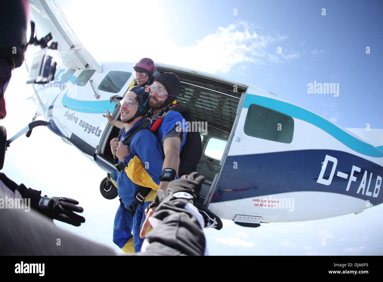 Skydivers están saltando juntos fuera de la aeronave. Un puente es hacer un bautizo de vuelo fijo a un salto profesional master. Imagen De Stock