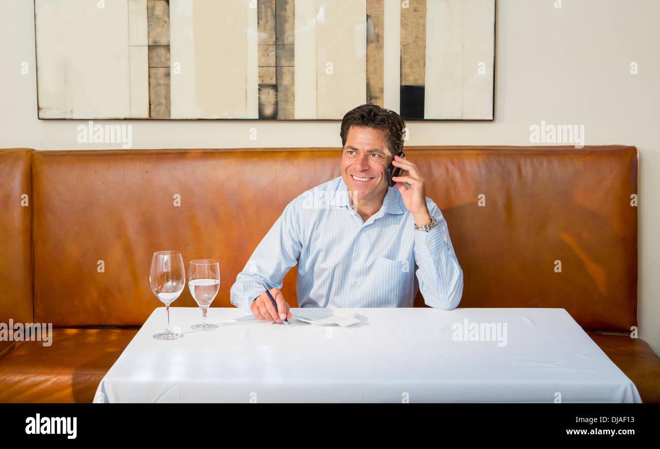 Empresario del Cáucaso en el móvil en el restaurante Foto de stock