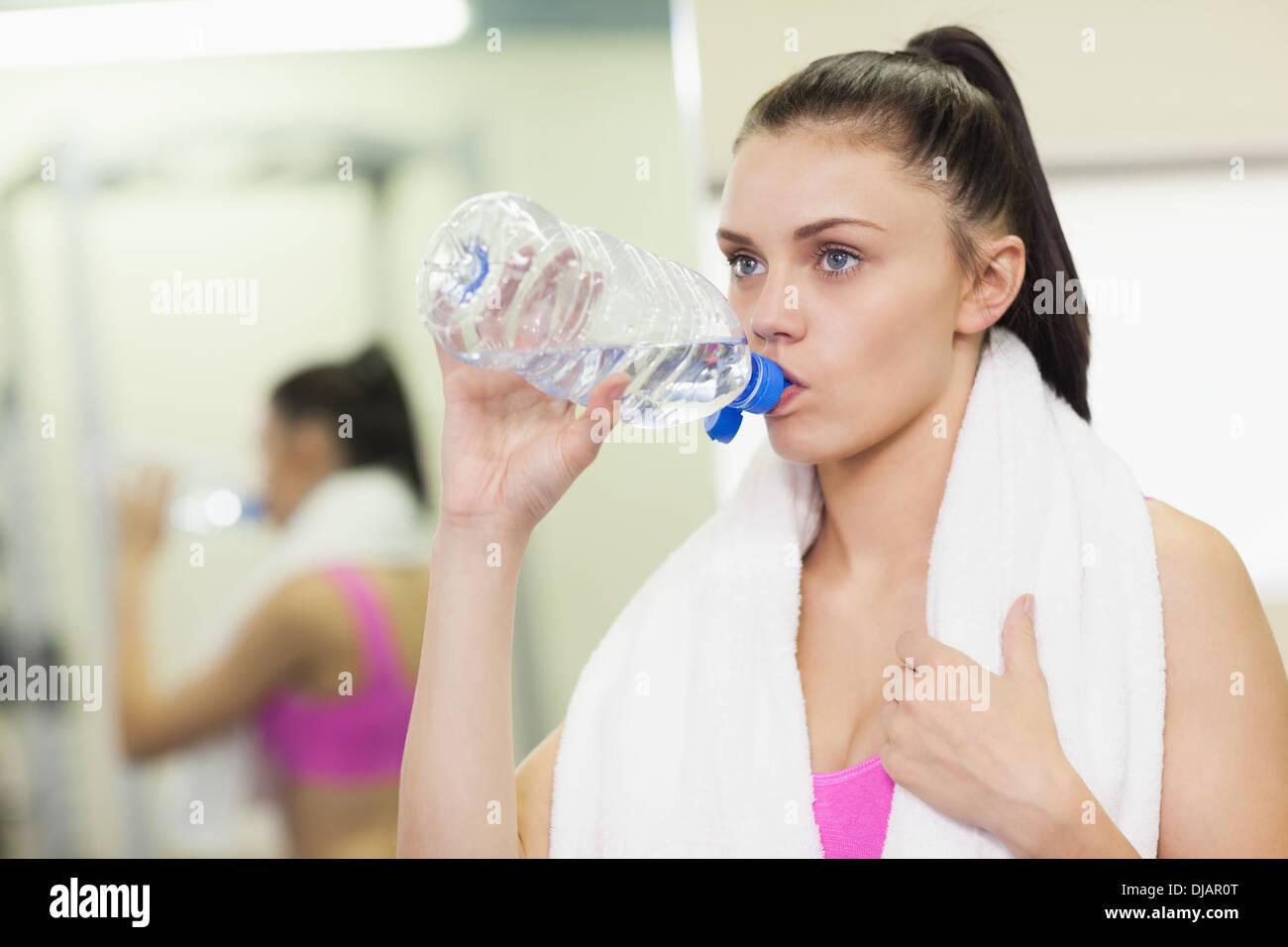 Cerca de una mujer en el gimnasio de agua potable Imagen De Stock