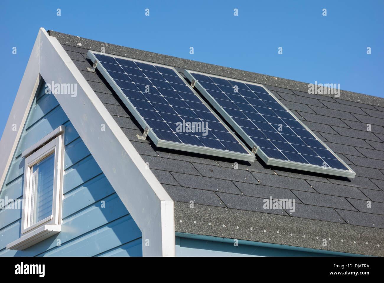 Paneles solares en el techo de la cabaña en la playa, el puerto de Christchurch, Dorset, Inglaterra, Reino Unido. Imagen De Stock