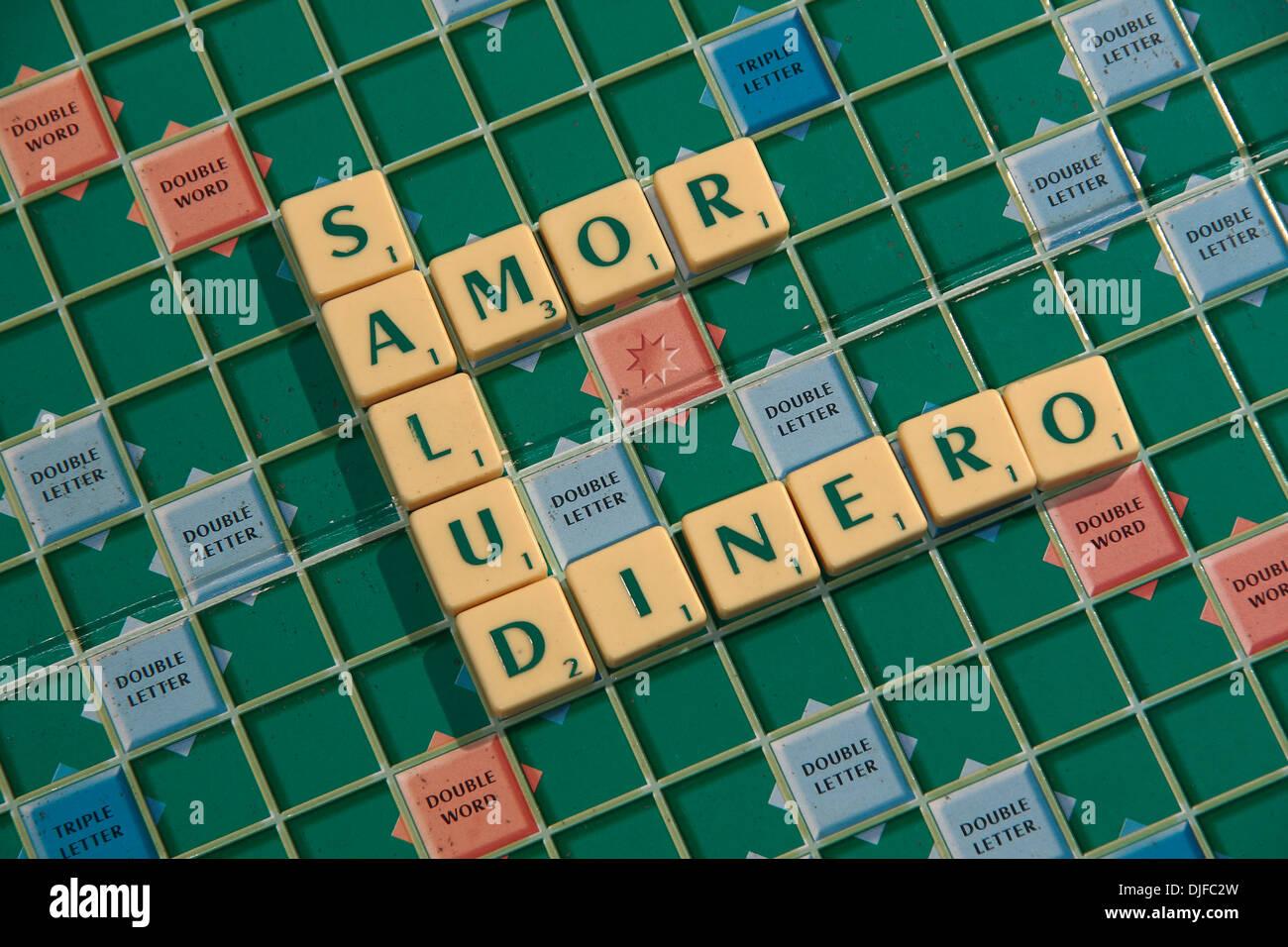 La frase española, 'salud amor y dinero' (salud, amor y dinero) escrito en el Scrabble azulejos, sobre un tablero de Scrabble. Imagen De Stock