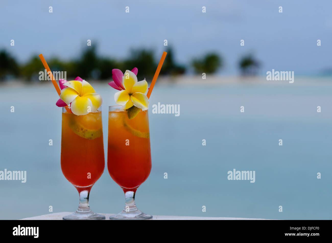 Al aire libre se sirven cócteles tropicales en Pacific Island Resort con agua de color turquesa en el fondo. Foto de stock