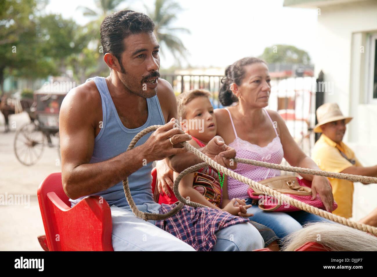 Una familia cubana compuesta por una madre, un padre y un hijo, en un caballo y una carroza, La Habana, Cuba, El Foto de stock