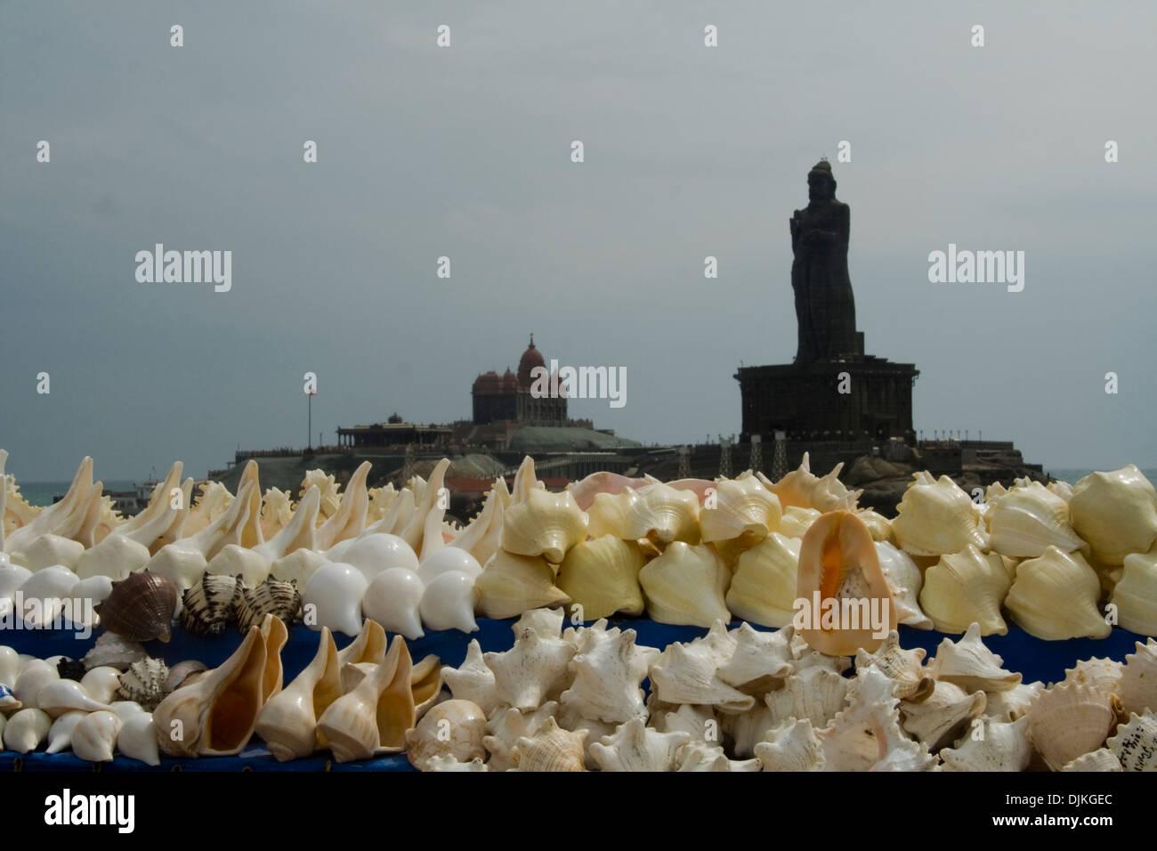 Variedad conchas de mar en la pantalla para los turistas con monumentos de roca en el telón de fondo en Kanyakumari, Foto de stock