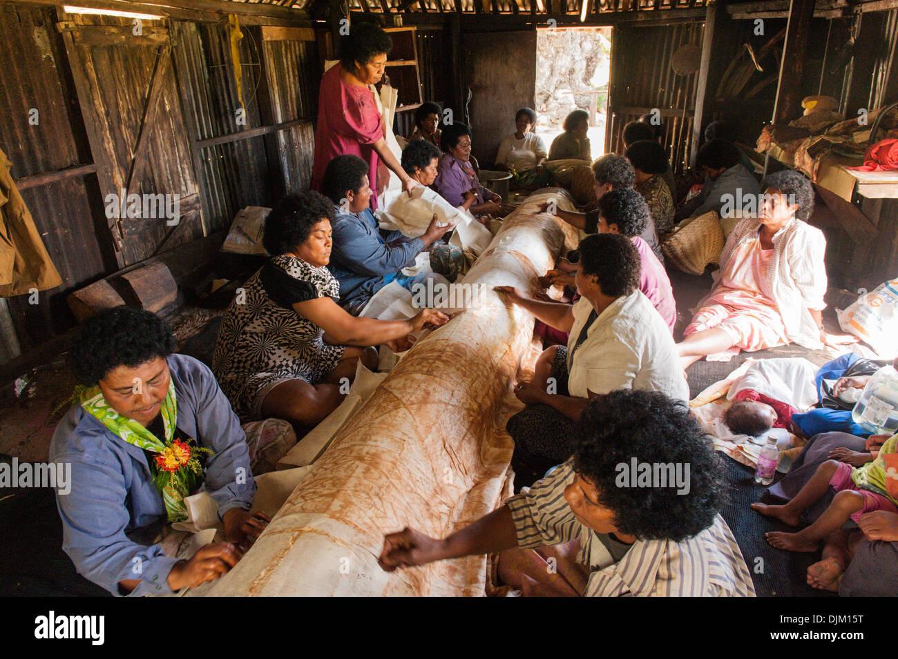 Gran grupo de mujeres que trabajan juntas en cuanto al estarcido en tela de corteza normal para hacer un gran paño impreso tradicional llamado trap. Fiji Imagen De Stock