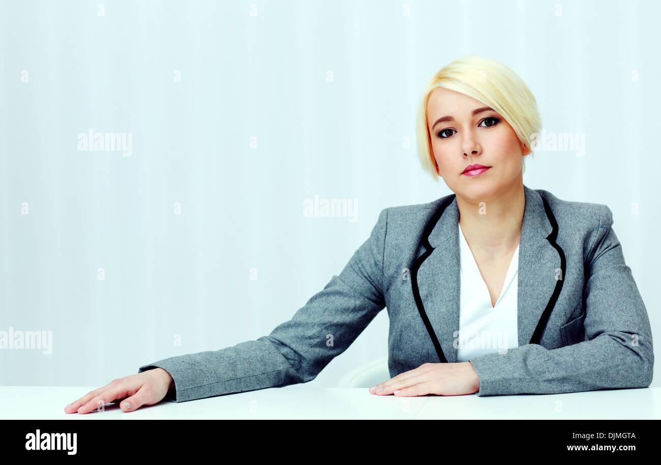 Retrato de una joven mujer pensativa sentado a la mesa en la oficina Foto de stock