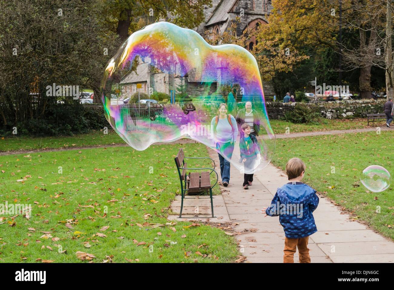 Un joven se divierte con una gigantesca burbuja de jabón que muestra los colores del arco iris y la gente sonríe en Betws-y-Coed, Conwy, North Wales, REINO UNIDO Imagen De Stock