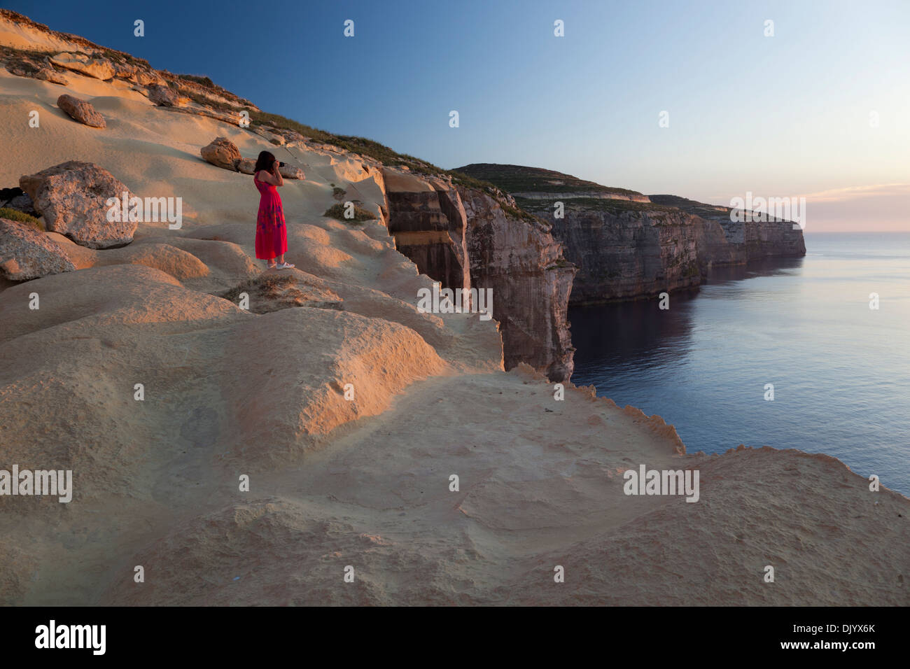 Una mujer que toma imágenes de la puesta de sol desde la cima de la seacliffs en el noroeste de la costa de Gozo. Imagen De Stock