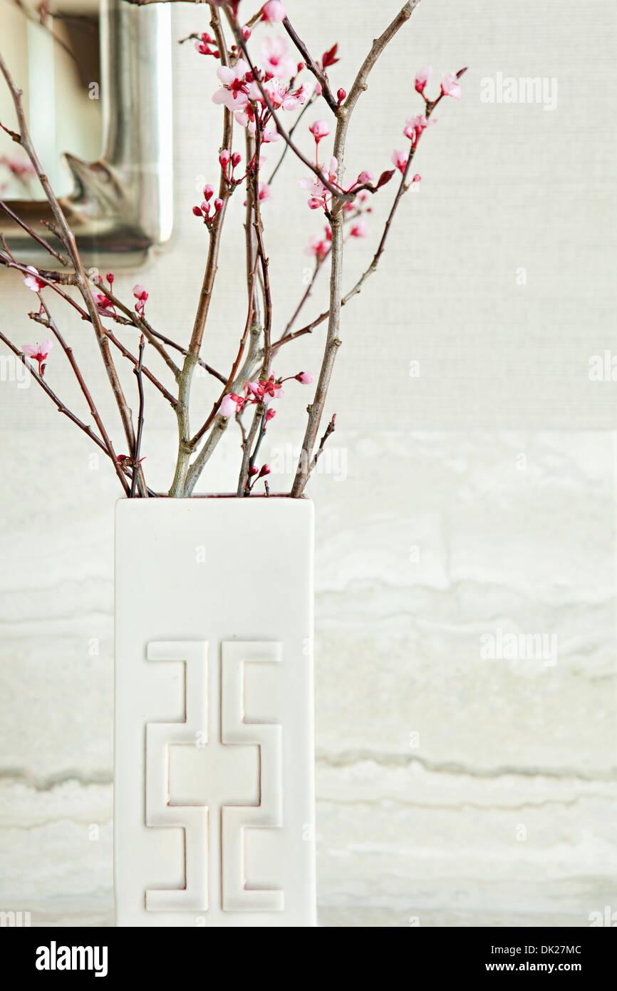 Cerca de flores rosadas en ramitas en jarrón blanco y moderno. Imagen De Stock