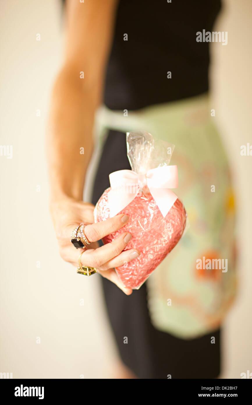 Cerca de la mitad del torso de mujer en delantal celebración envuelto en forma de corazón el Día de San Valentín cookie Imagen De Stock