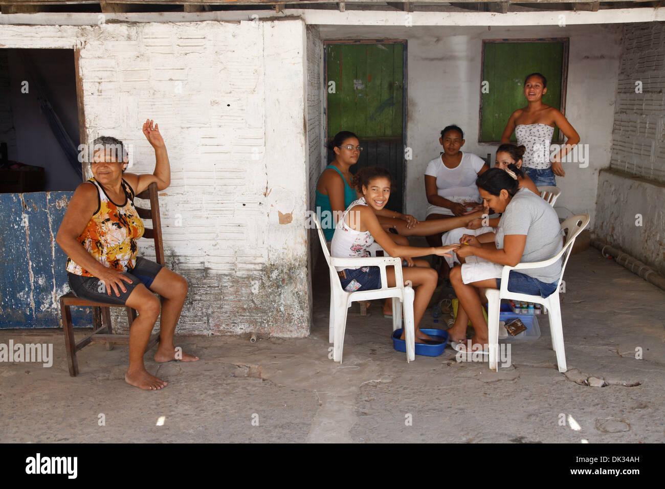 Las mujeres locales haciendo sus uñas en la casa sombra, Cumbuco, distrito de Fortaleza, Brasil. Imagen De Stock