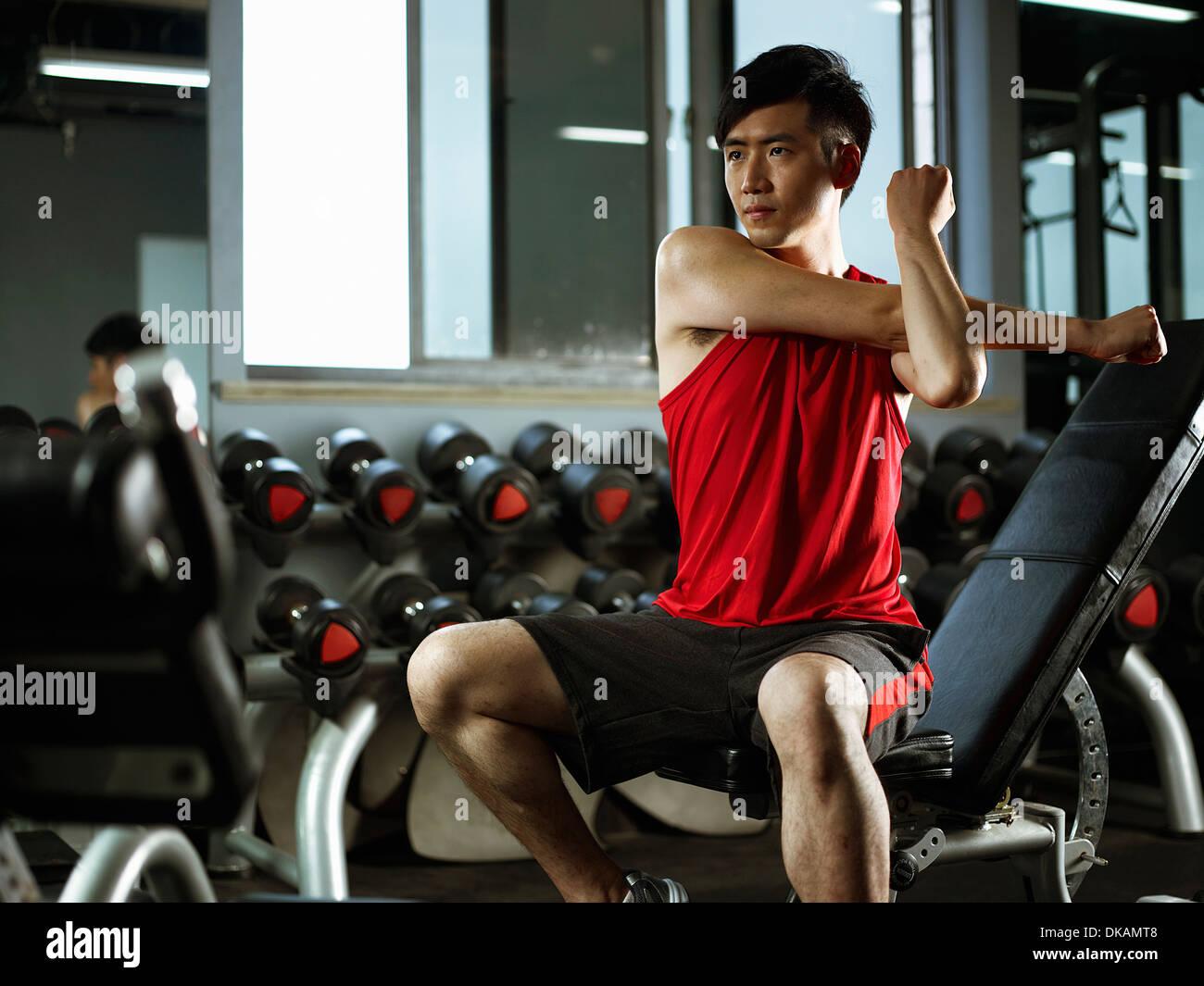 Hombre sentado en el banquillo de peso beber estiramiento para calentar Imagen De Stock