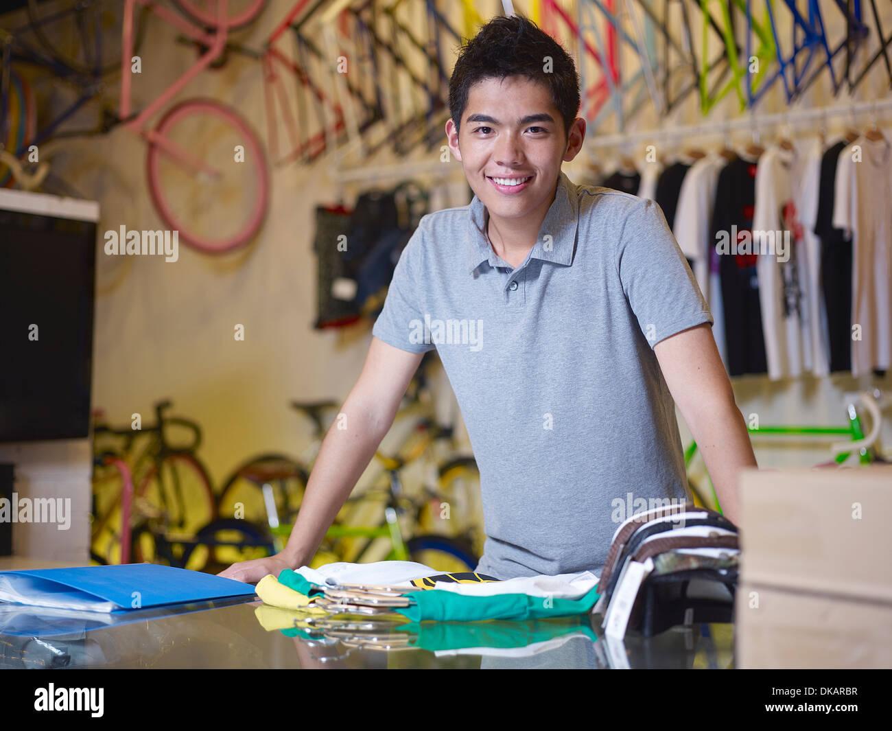 Retrato de joven mirando a la cámara en la tienda de bicicletas Imagen De Stock