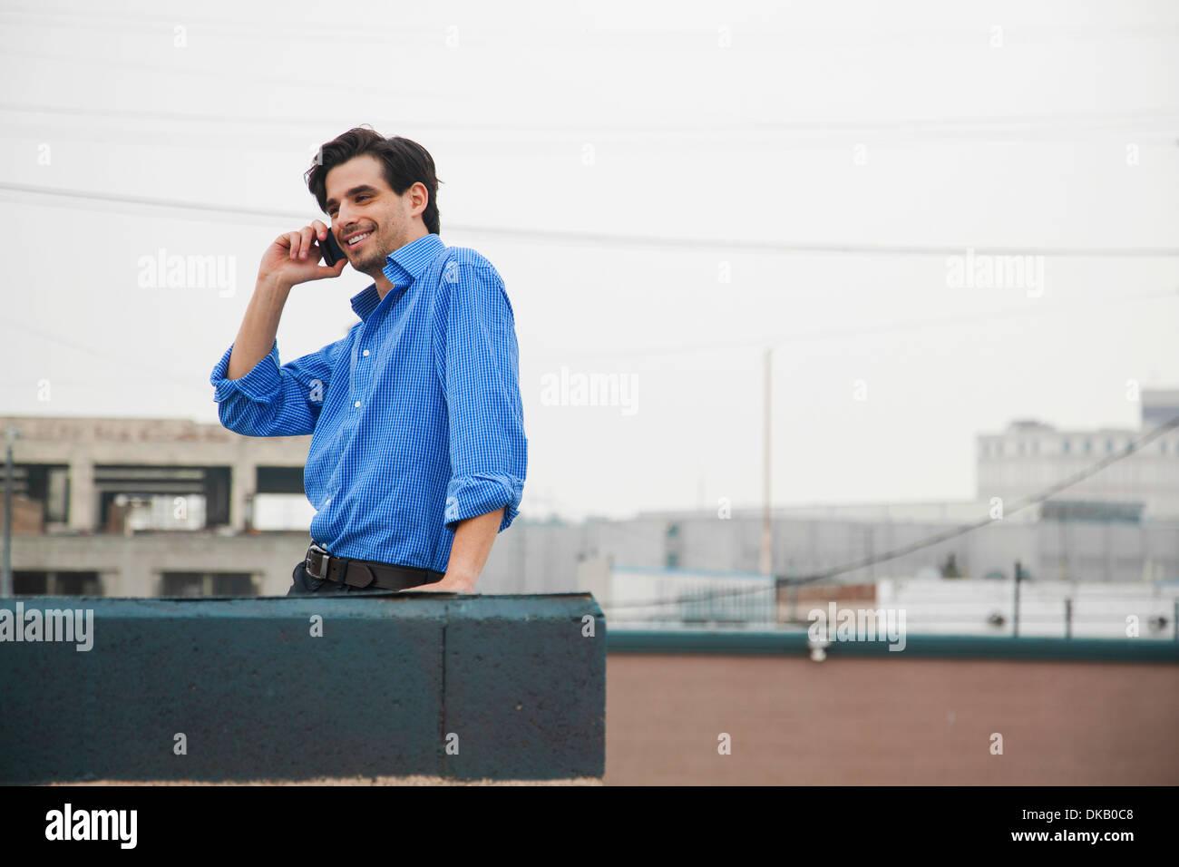 Seguro joven utilizando mobile en la azotea de la ciudad Imagen De Stock