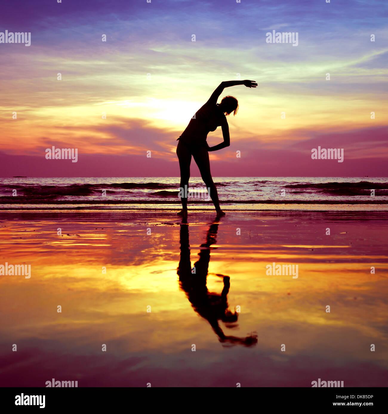 Silueta de mujer joven, ejercicios de estiramiento del yoga en la playa en el atardecer. Foto de stock