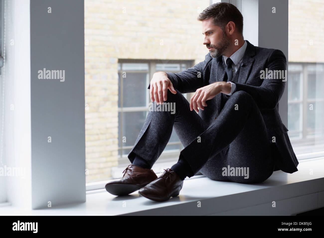 Retrato del hombre de negocios sentada sobre el alféizar mirando afuera de la ventana Imagen De Stock