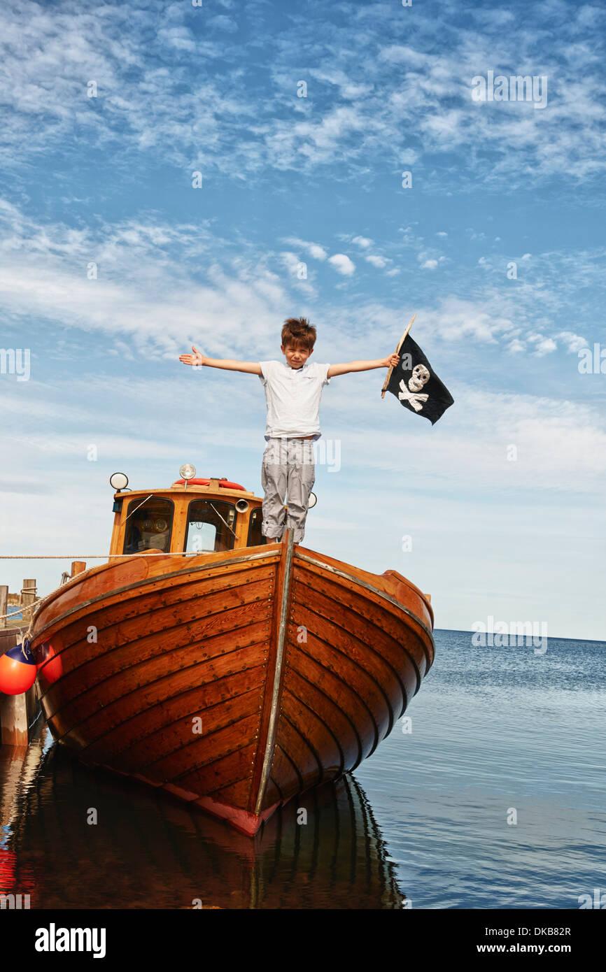 Retrato de niño en el barco de bandera pirata, Eggergrund holding, Suecia Imagen De Stock