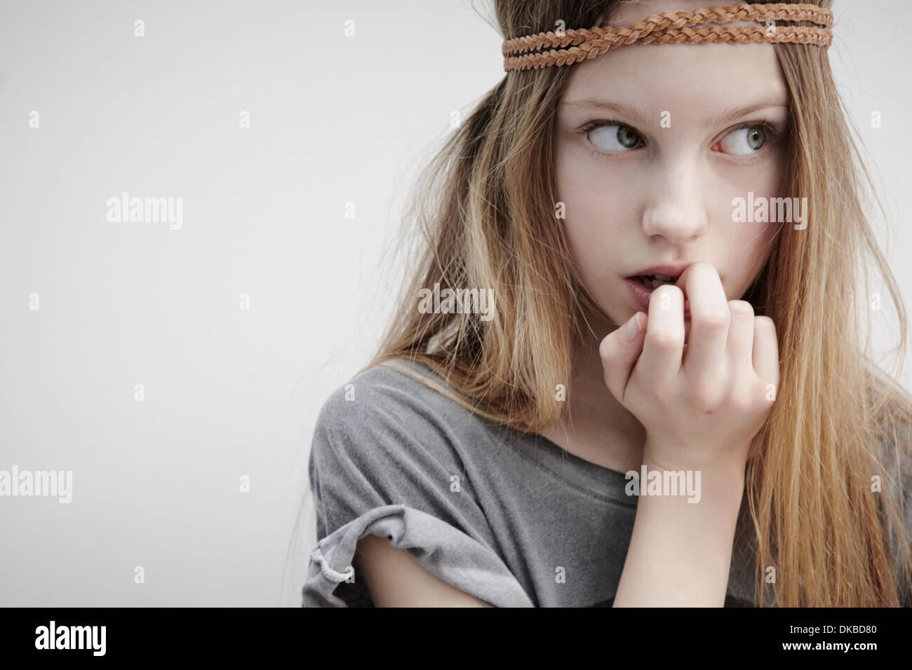 Retrato de vestida de cuero trenzado alrededor de la cabeza, sosteniendo hacia abajo, los dedos en la boca Imagen De Stock
