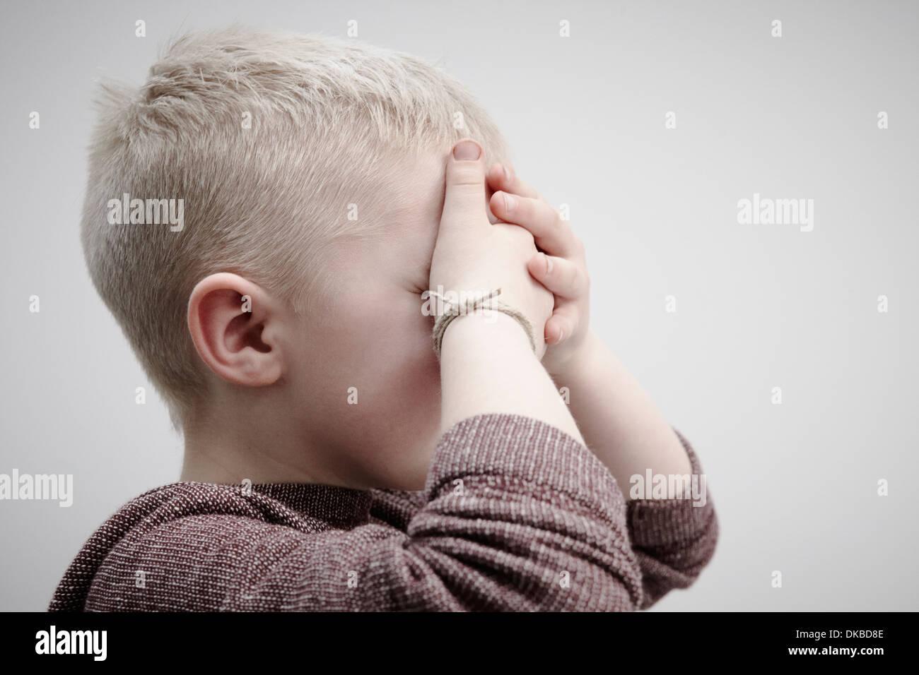 Retrato de niño usando brown puente, cubriendo la cara con las manos Imagen De Stock