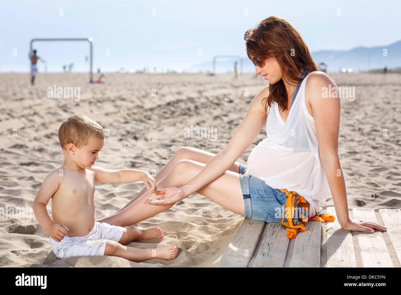 Bebé en la playa de arena de vuelco en la mano de la madre Foto de stock
