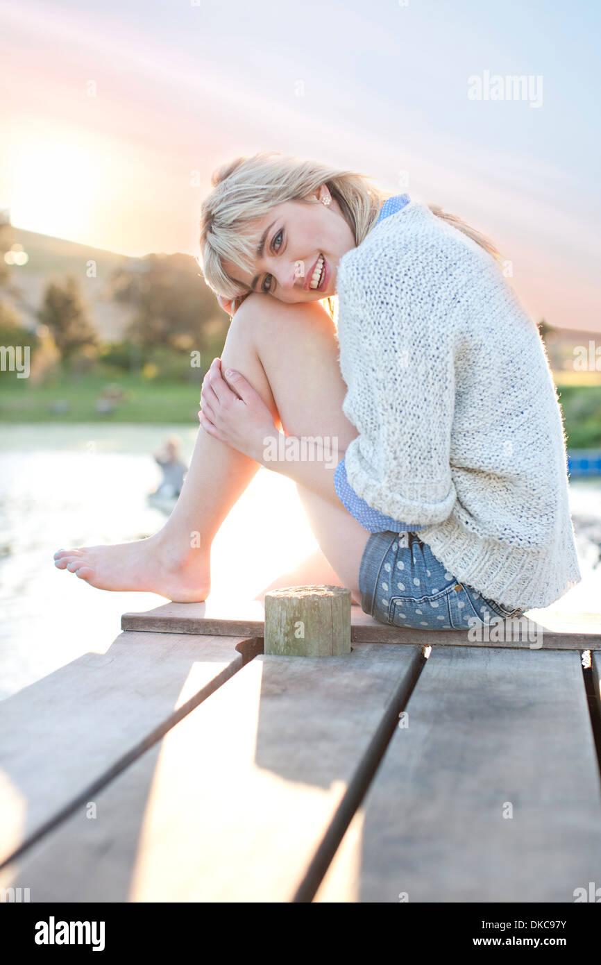 Tímido joven sentado en el muelle Imagen De Stock