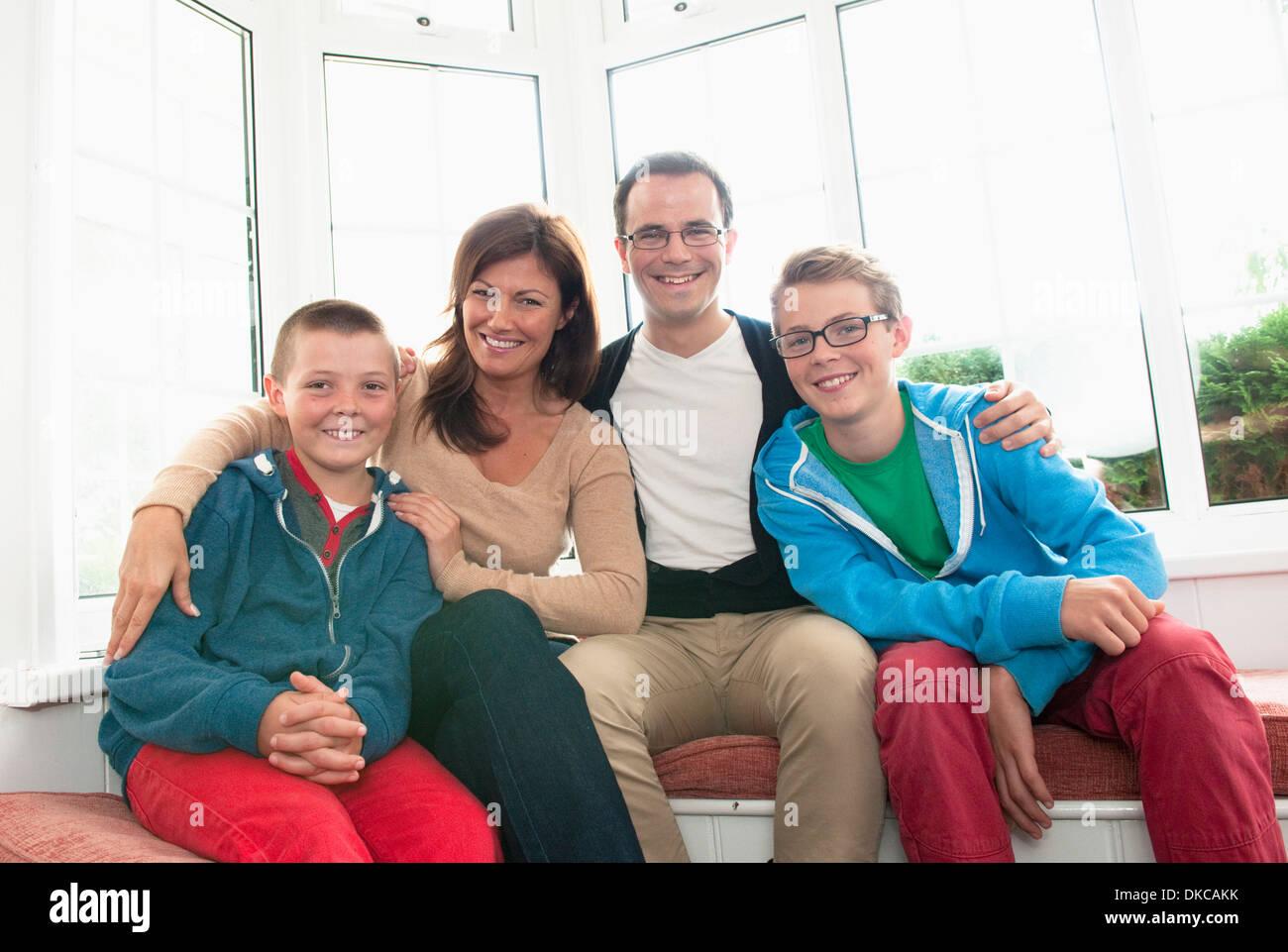 Retrato de familia delante de la ventana Foto de stock