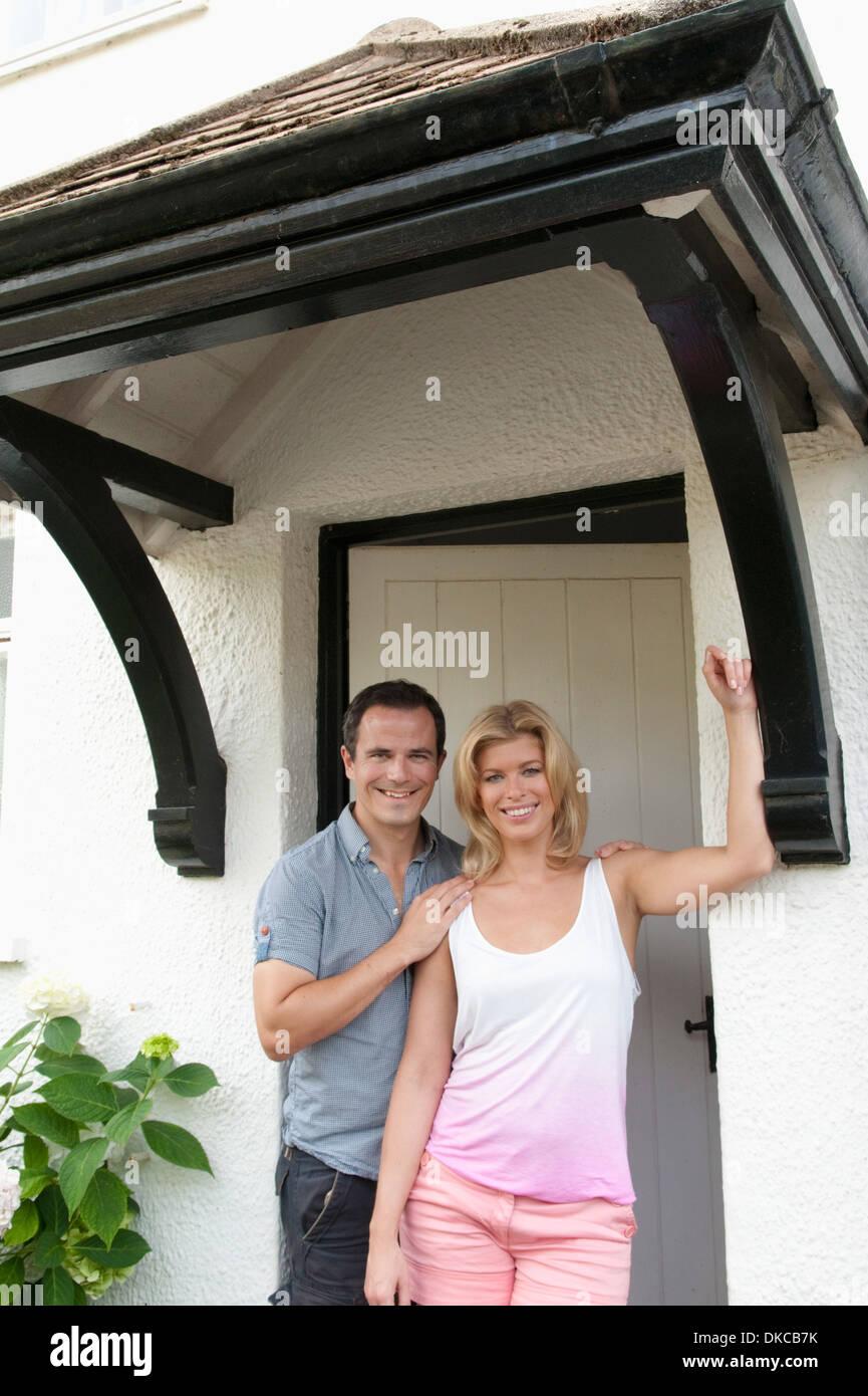 Adulto medio par de pie en la puerta frontal del nuevo hogar Imagen De Stock