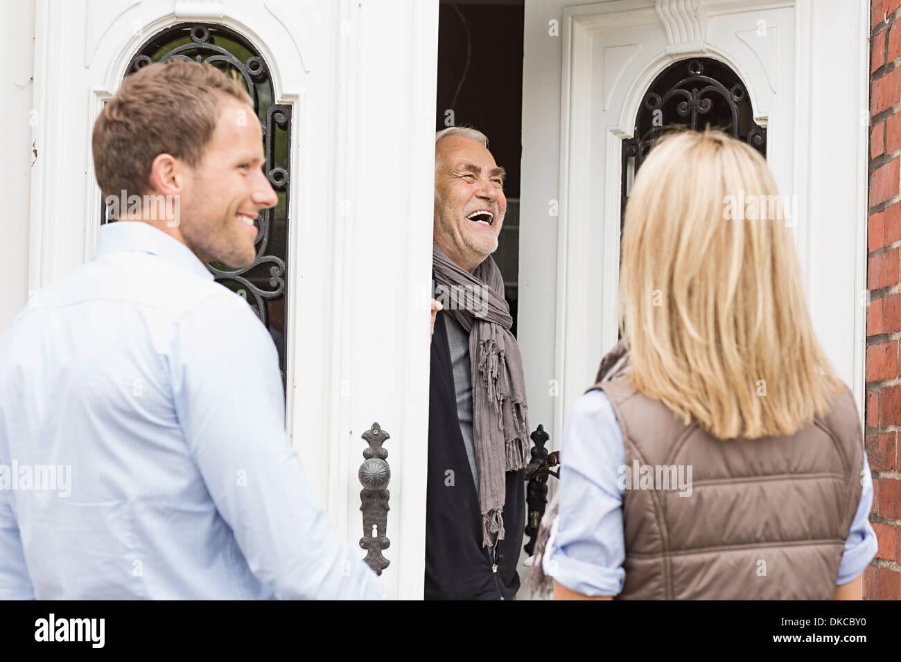 Padre abriendo la puerta delantera riendo Imagen De Stock