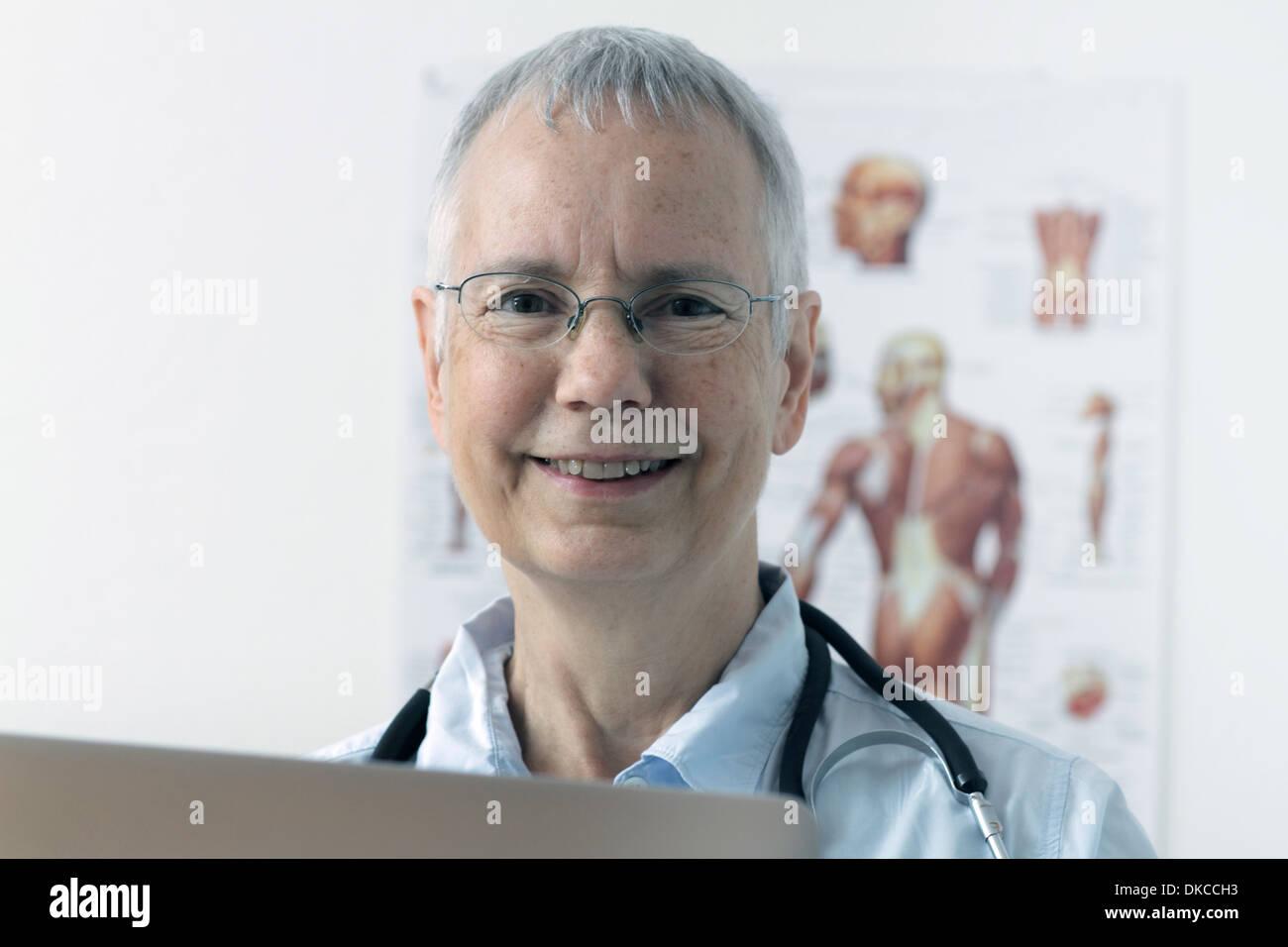 Una mujer reír doc con un músculo humano persona póster en el fondo y un portátil Imagen De Stock