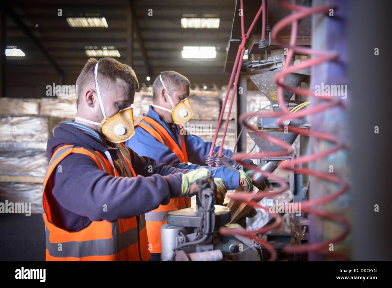 Los trabajadores de ropa de protección bolsas de llenado con minerales Imagen De Stock