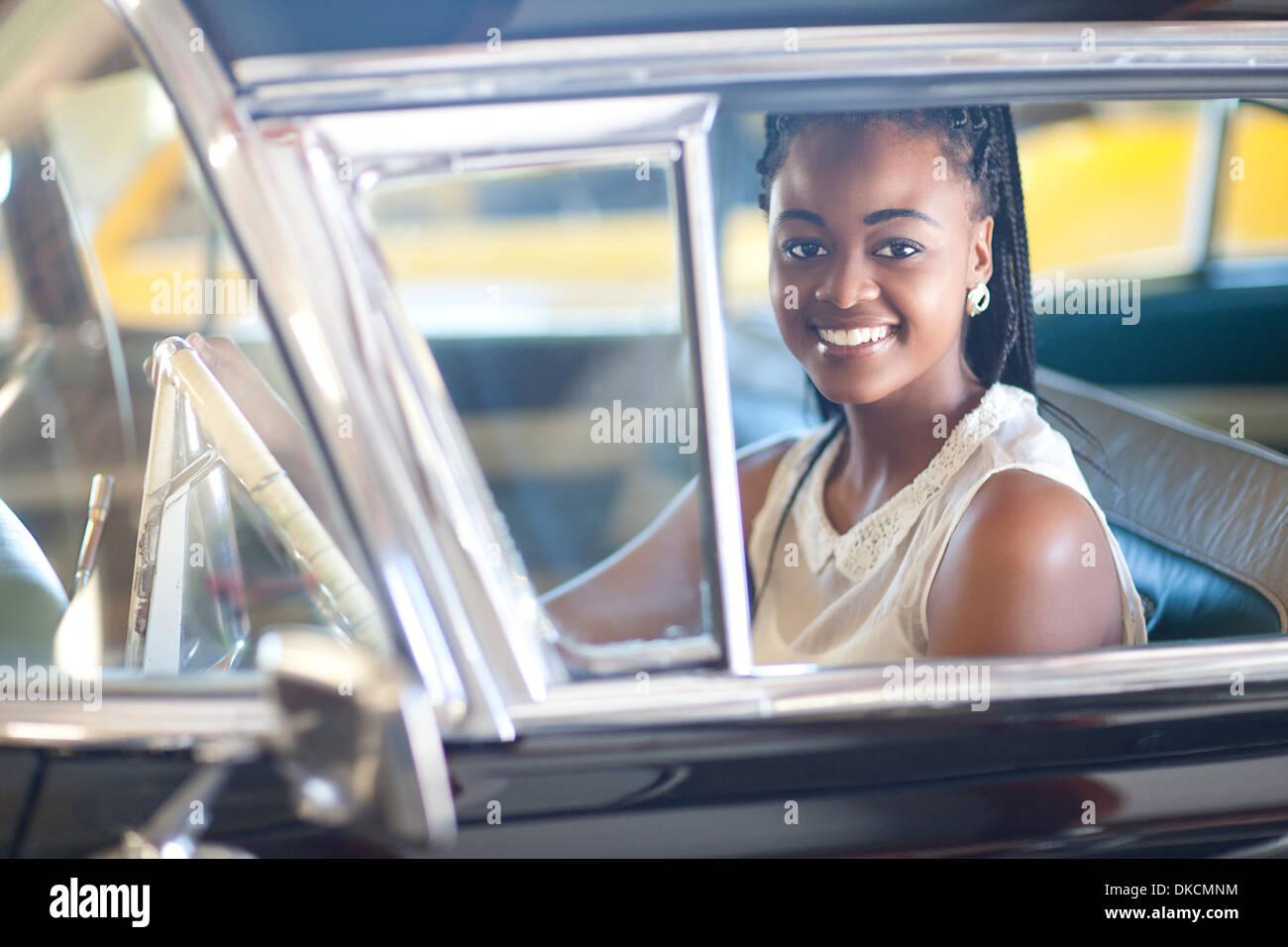 Mujer de peinado trenzado conducir coches antiguos Imagen De Stock
