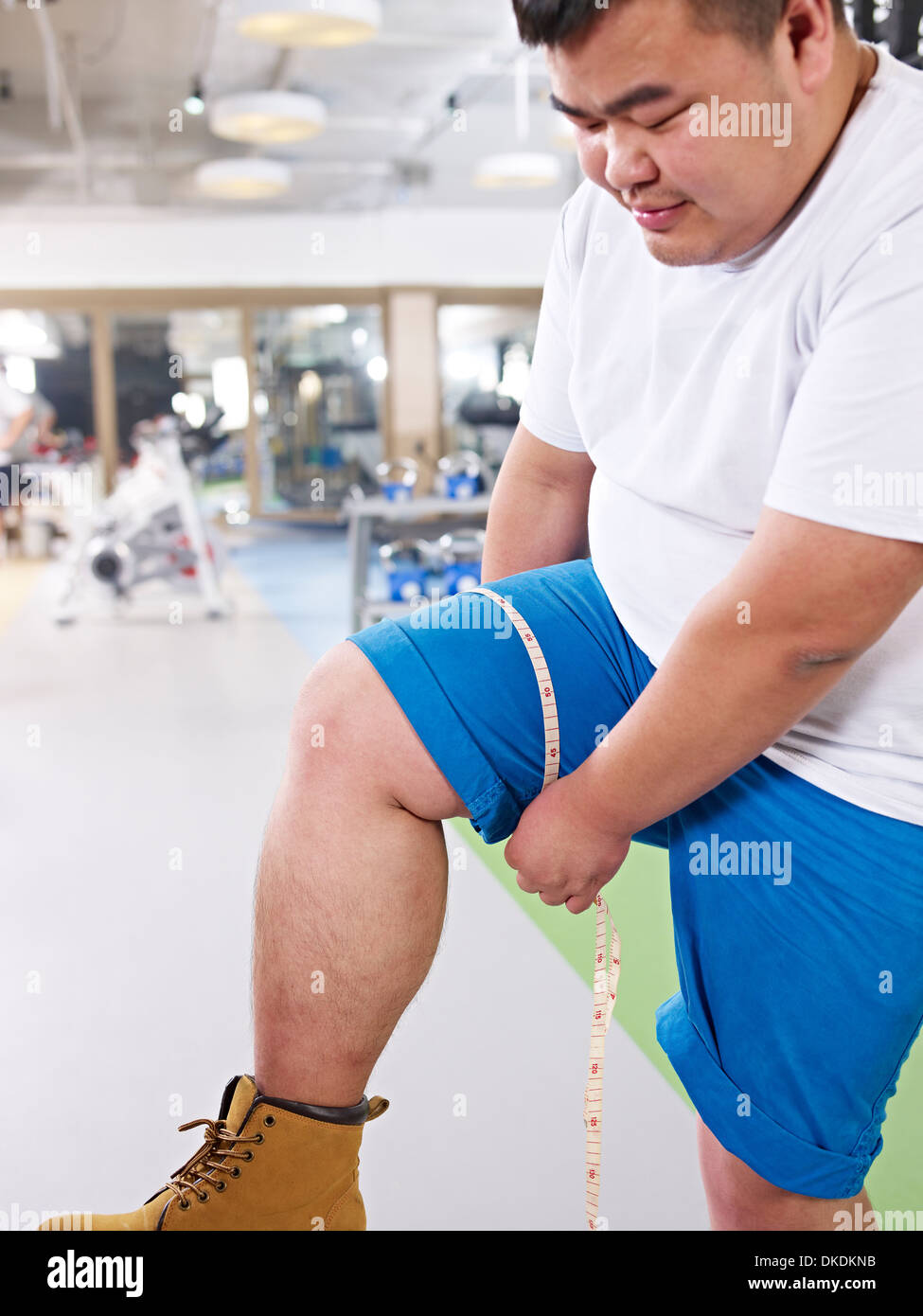 Hombre con sobrepeso midiendo el tamaño de la pierna Imagen De Stock