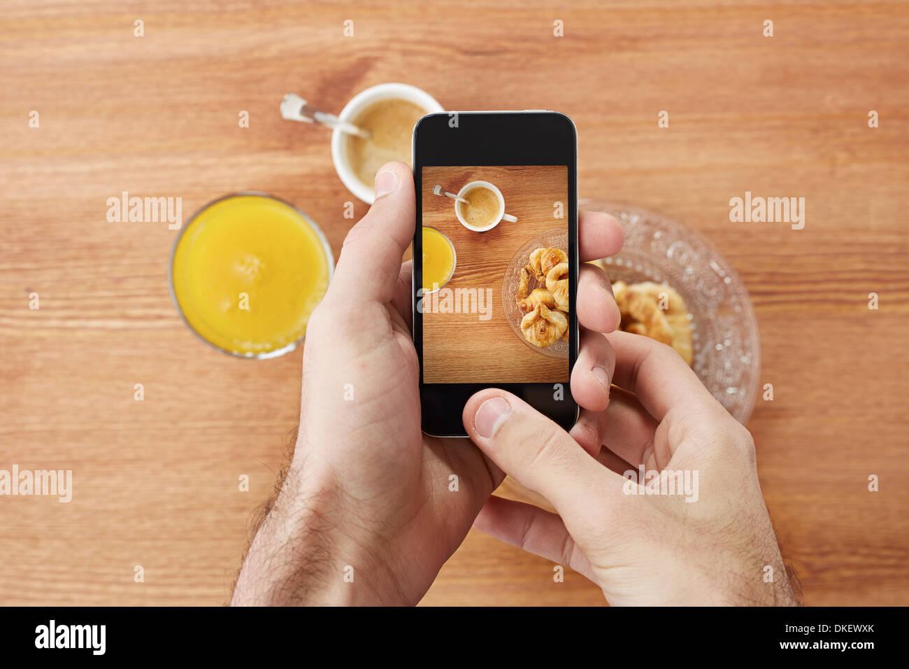 Manos tomando fotos de desayuno que incluye croissants, café y zumo de naranja con el smartphone Foto de stock
