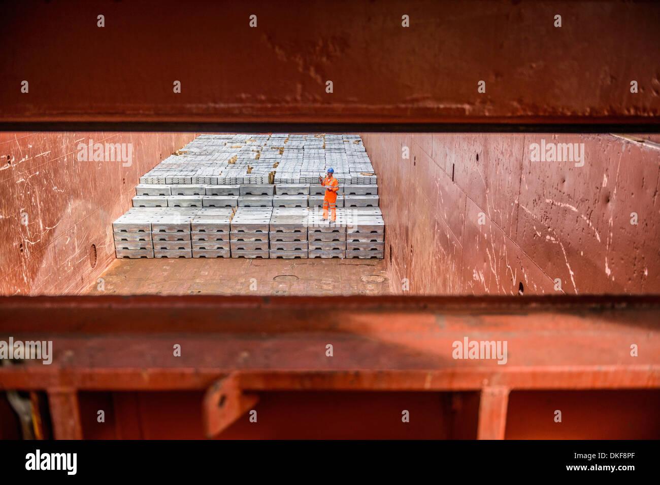 Comprobación del trabajador lingotes de metal en la bodega del barco Imagen De Stock