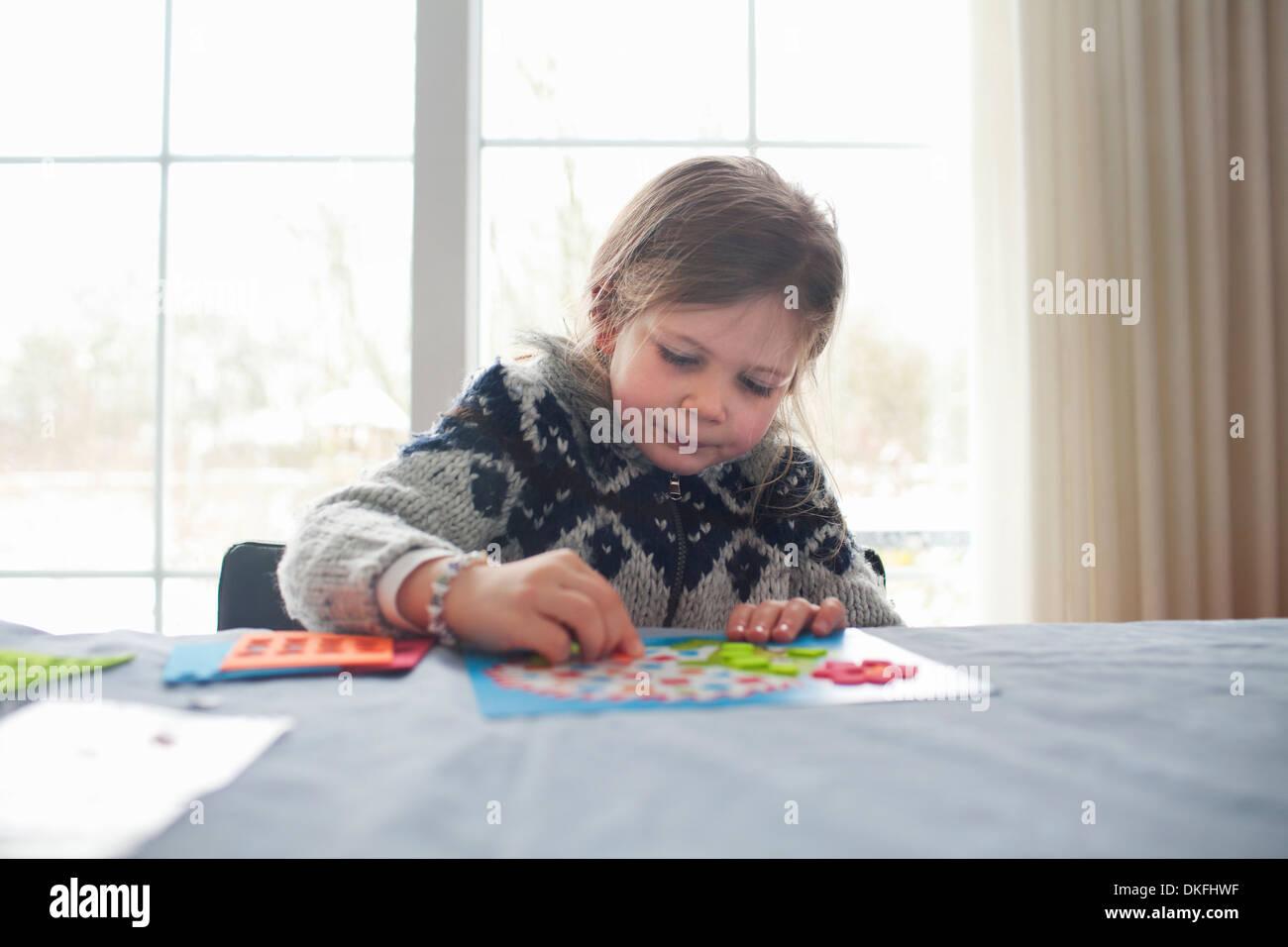 Muchacha sentada a la mesa, concentrándose en juego Foto de stock