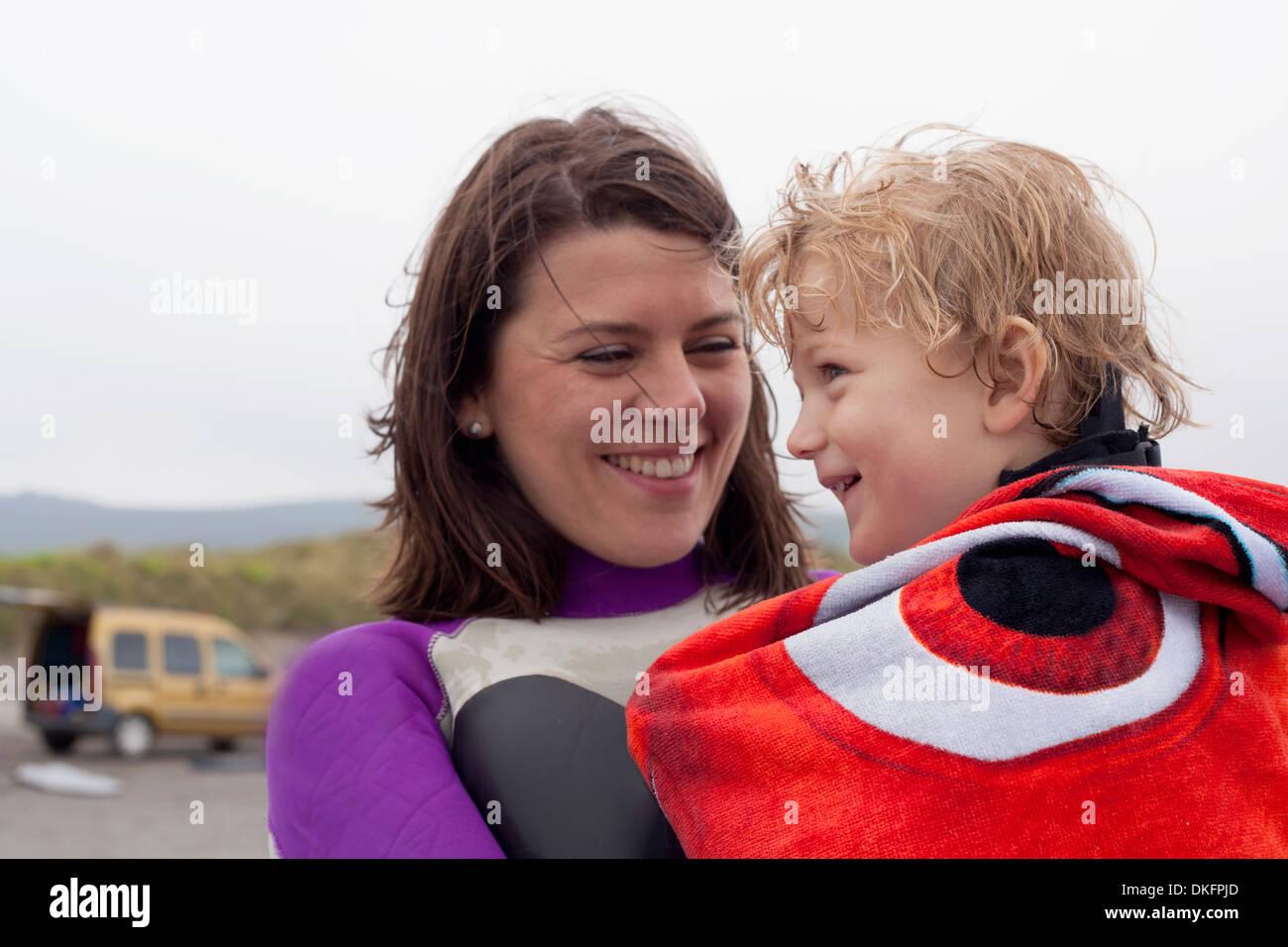 Retrato de madre sosteniendo hijo envuelta en una toalla Imagen De Stock