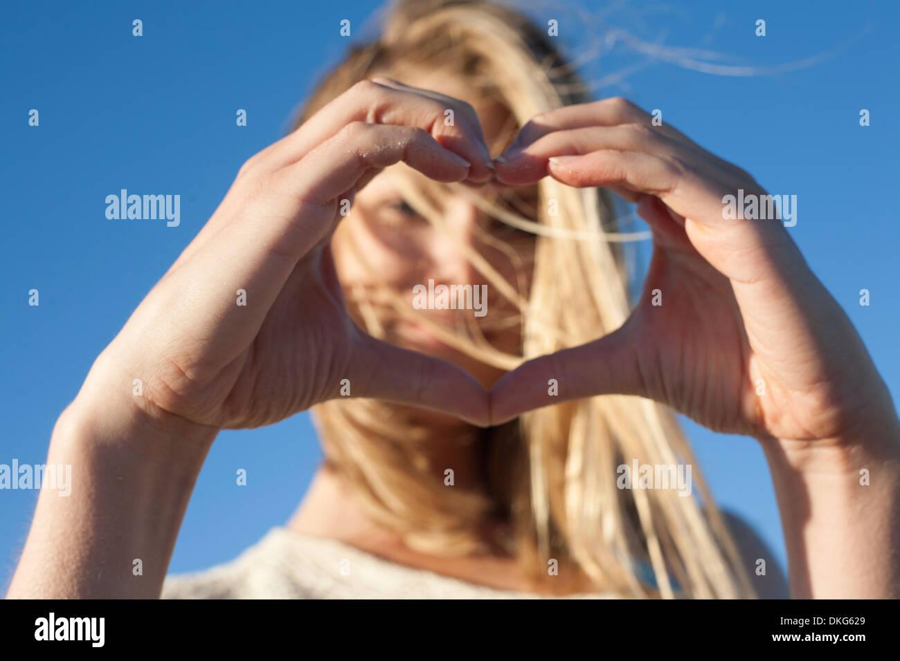 Joven de corazón hacer firmar con las manos, Breezy Point, Queens, Nueva York, EE.UU. Imagen De Stock