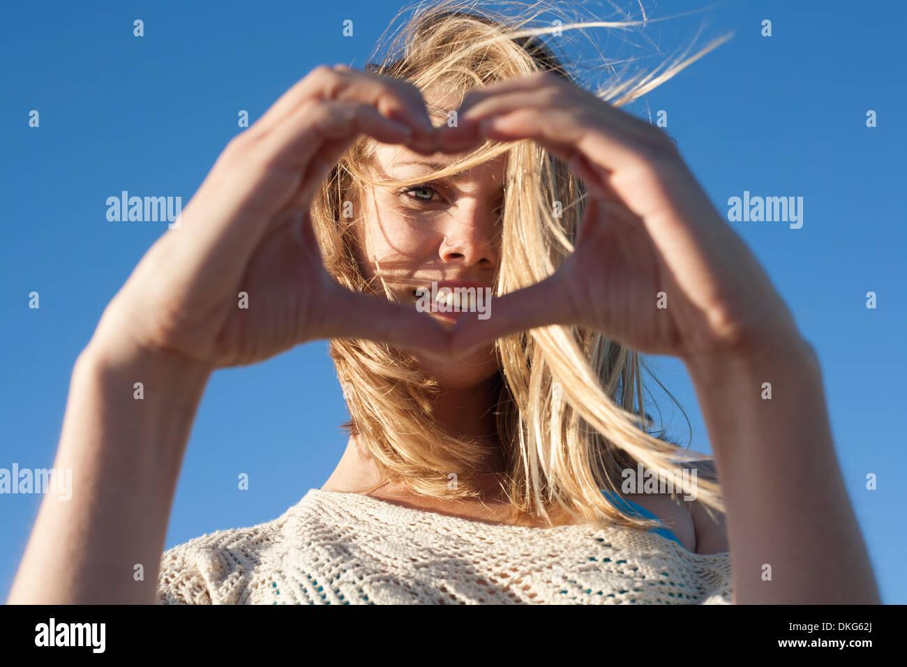 Retrato de mujer joven corazón hacer firmar, Breezy Point, Queens, Nueva York, EE.UU. Imagen De Stock