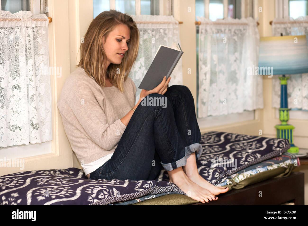 Mujer joven libro de lectura en el asiento de ventana Foto de stock