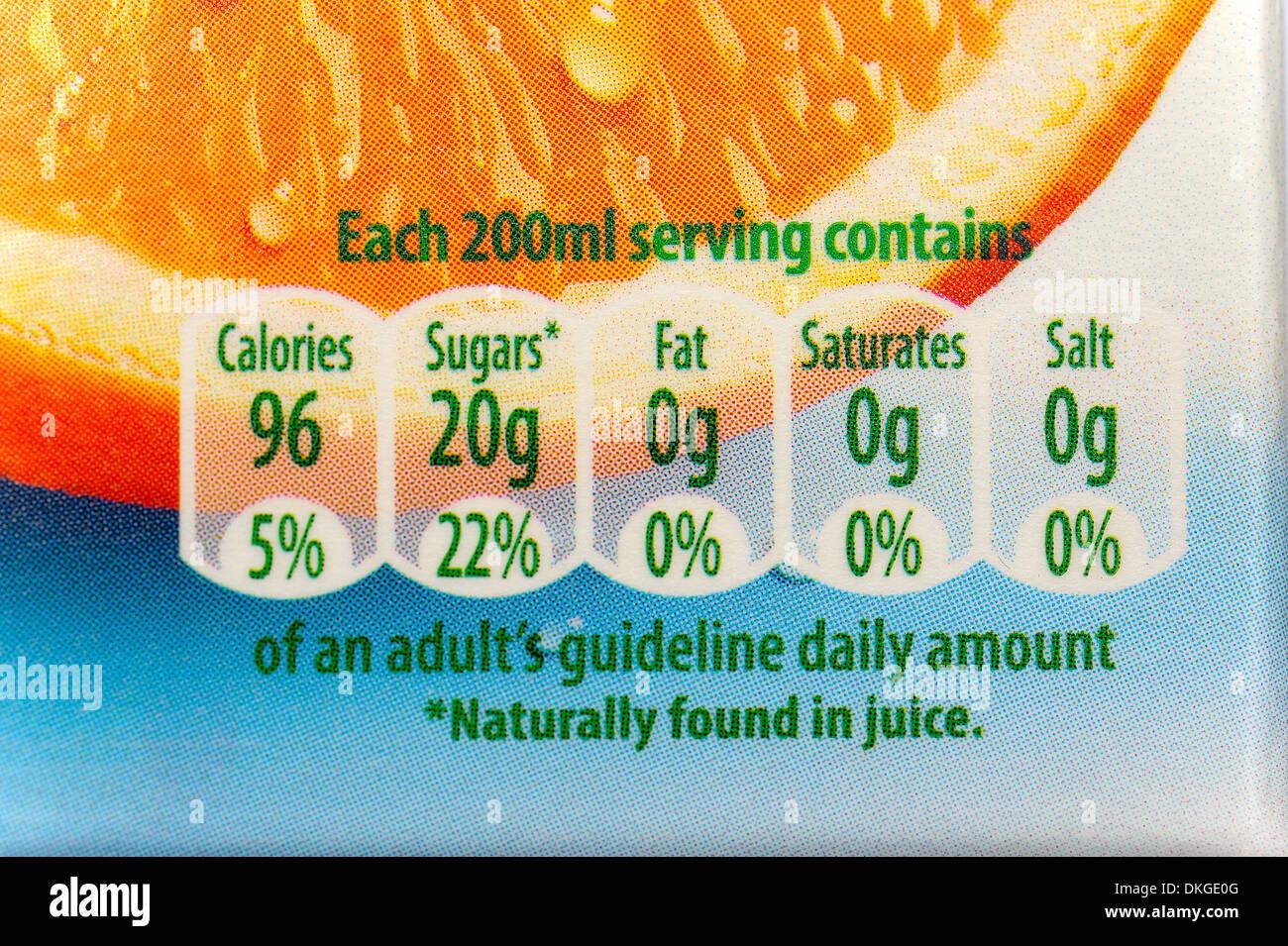 Los adultos diariamente directrices en calorías, azúcares, grasas,satura,y sal encontrados en un cartón de zumo de naranja. Imagen De Stock