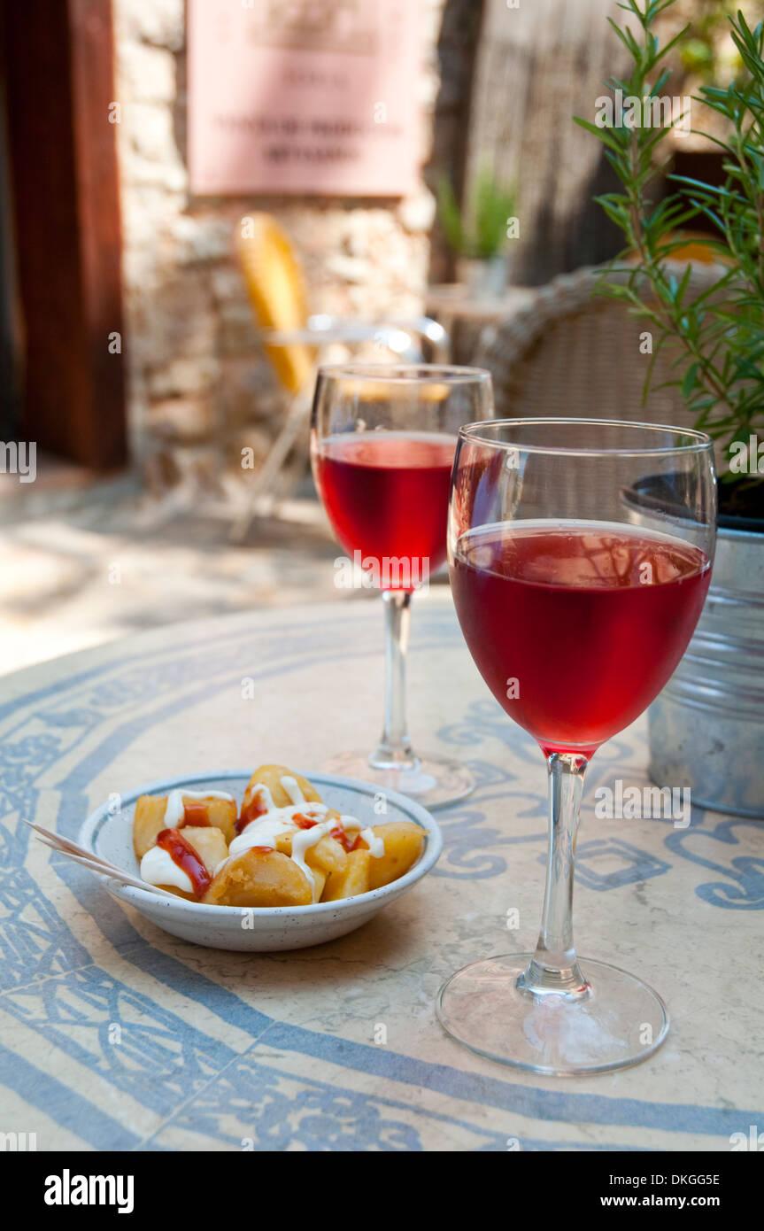 Aperitivo español: dos copas de vino rosado con tapas en la terraza. Imagen De Stock