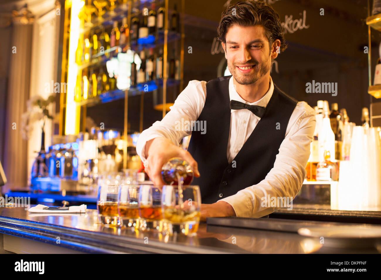 Bien vestida barman vertiendo en bourbon bar de lujo Imagen De Stock