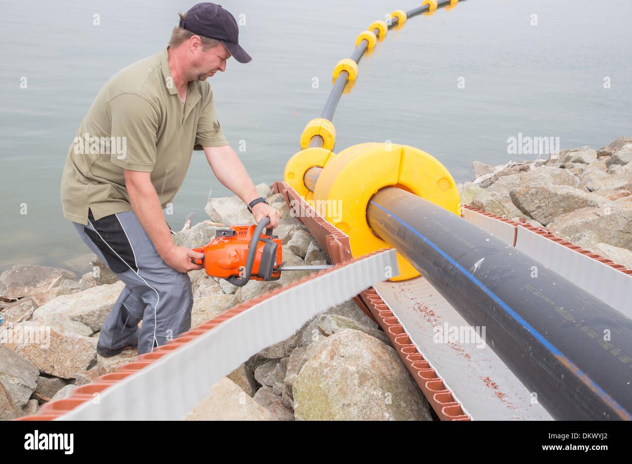 Trabajador en el trabajo con la sierra eléctrica Foto de stock