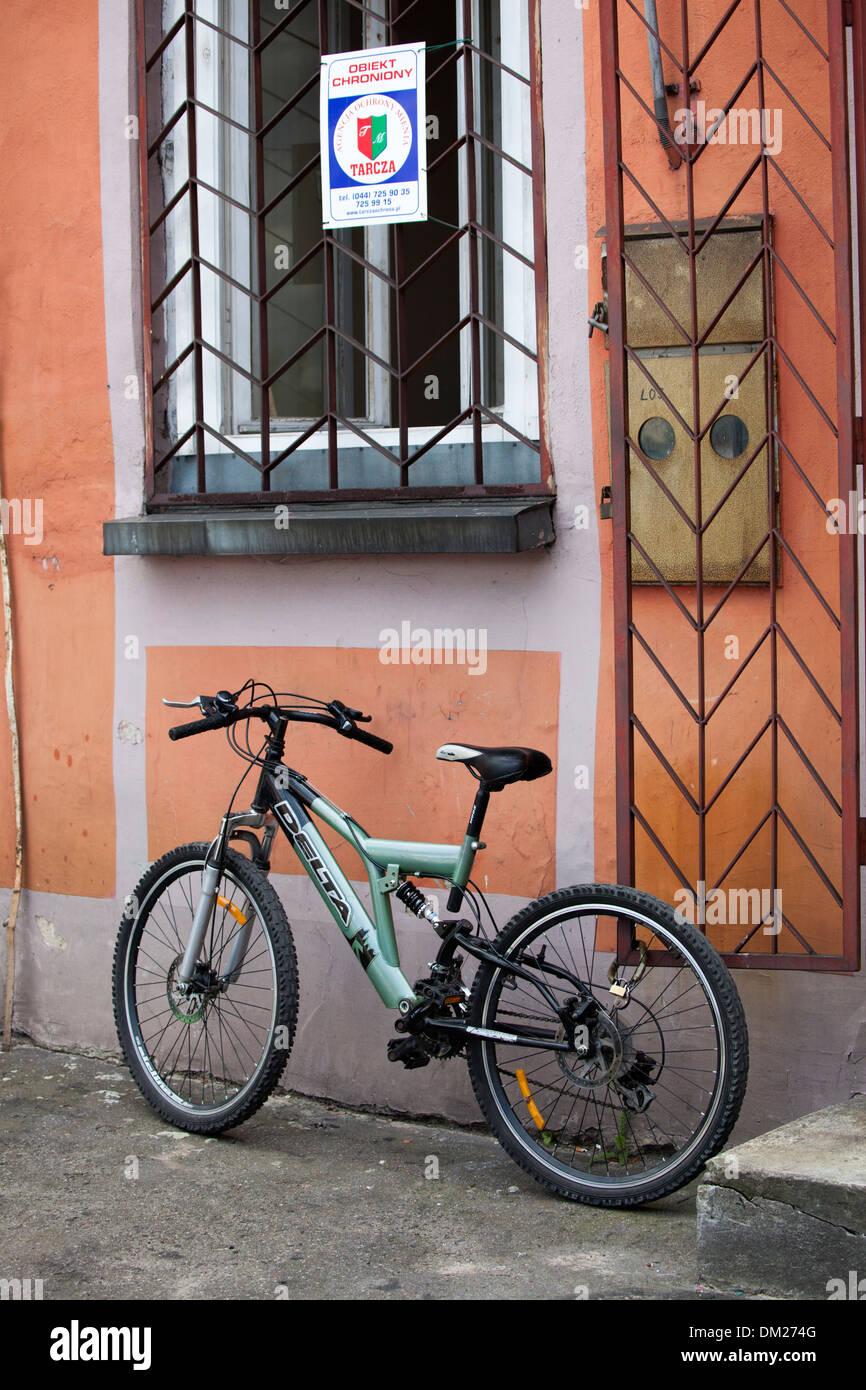 Alta tecnología - bicicleta debajo de una ventana cerrada y entrada con un signo de seguridad. Tomaszow Mazowiecki Polonia Central Imagen De Stock