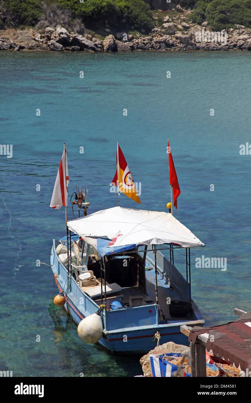 Barco de pesca de agua azul y la península de Karpas, Norte de Chipre el 26 de mayo de 2013 Imagen De Stock