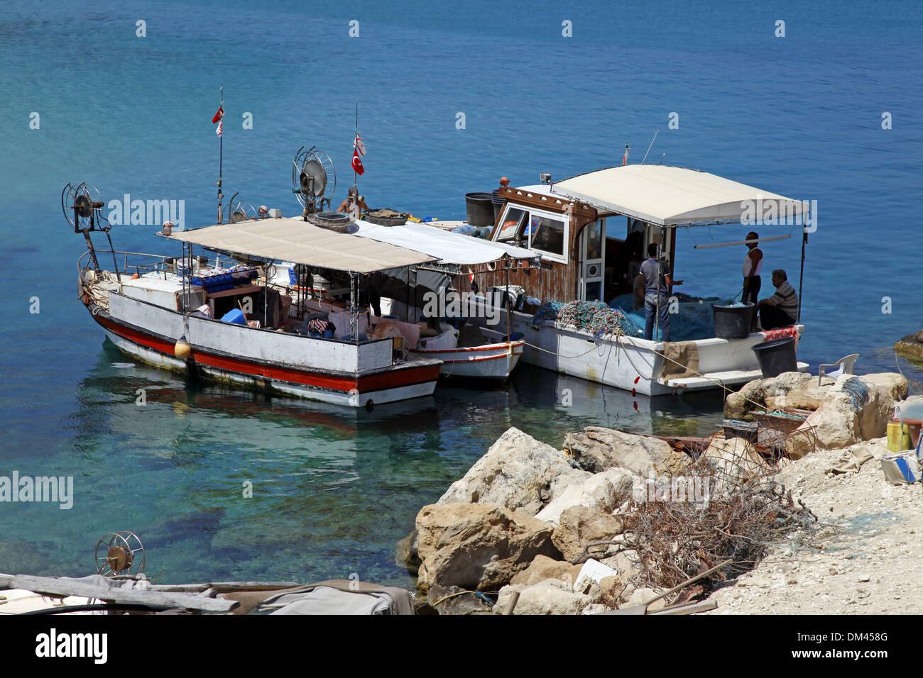 Barcos de pesca y agua azul de la península de Karpas Chipre Septentrional el 26 de mayo de 2013 Imagen De Stock