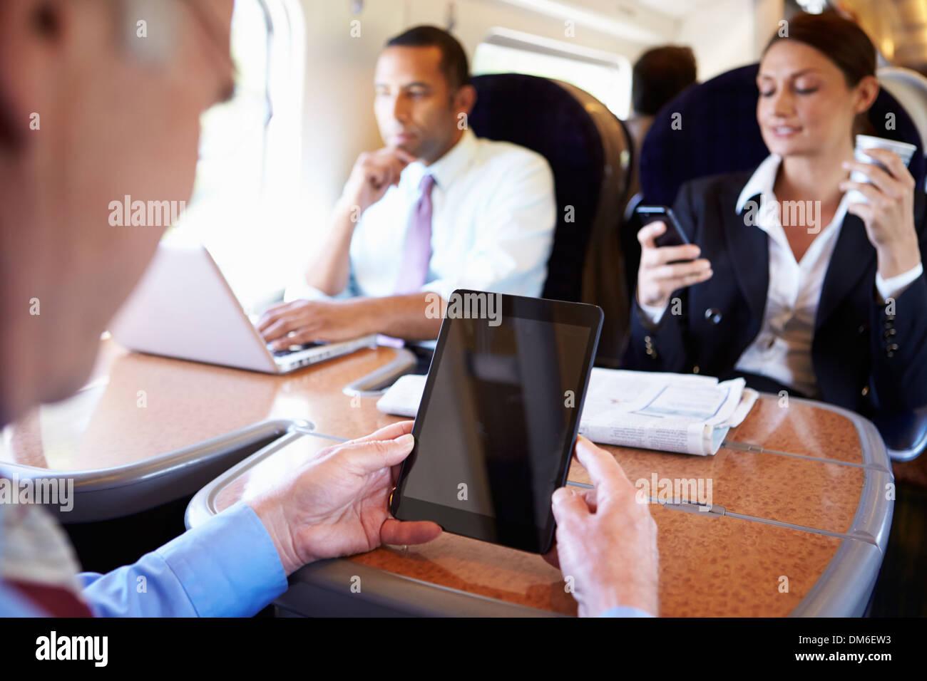 Empresarios en tren utilizando dispositivos digitales Foto de stock