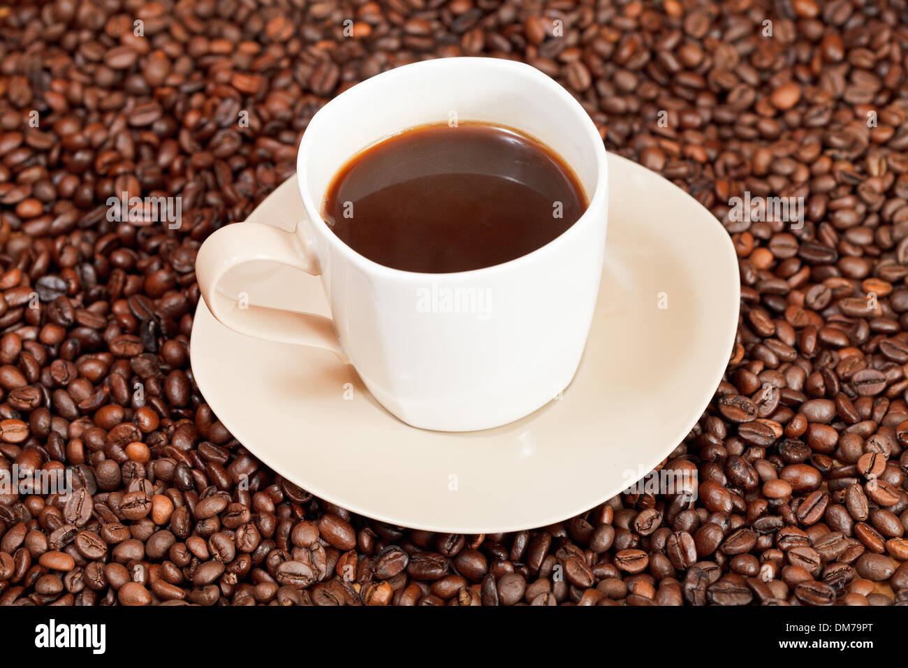 Taza de café sobre sauser y café tostado en grano Imagen De Stock